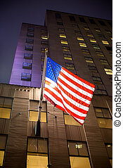 American flag with skyscrapers on background