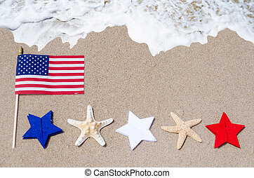 American flag with starfishes on the sandy beach - American...