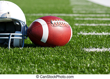 Football and Helmet on the Field - American Football and...