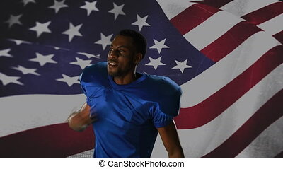 Close up of an African-american football player taunting with an American flag waving in the foreground