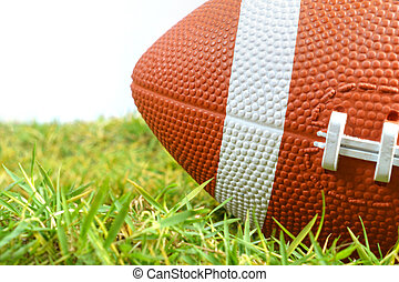 American Football ball on green grass isolated on white background