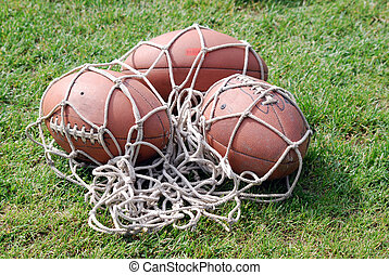 American football balls in net on field