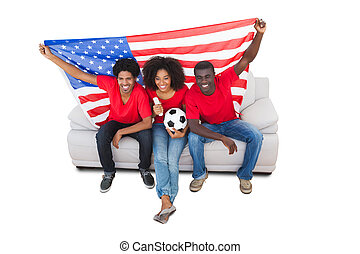 American football fans in red on the sofa