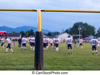 American football goal posts with blurred team