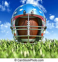 American football helmet over the oval ball, on the grass....