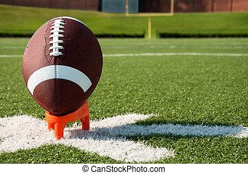 American Football Kickoff - American football on tee on...
