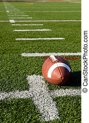 A brown leather American football on a green football field