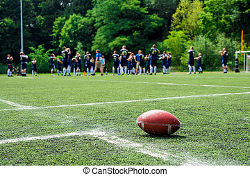 American football on field with team in background