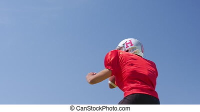 Low angle side view of a mixed-raced American football player catching and throwing a football, against a blue sky at a sports field, in slow motion. Track and Field Sports Training in Stadium.