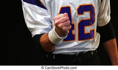 American football player clenching his fist before a big...