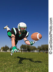 American football player diving and catching the ball