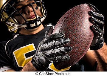 American football player holding ball