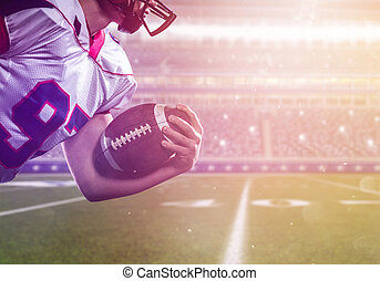 American football player holding ball while running on the field