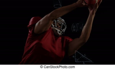 American football player jumping and catching a ball against black background