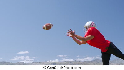 American football player jumping to catch a ball - Side view...