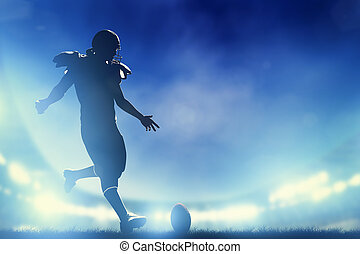 American football player kicking the ball, kickoff. Stadium lights