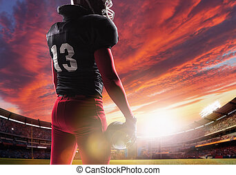 American football player posing with ball on stadium background