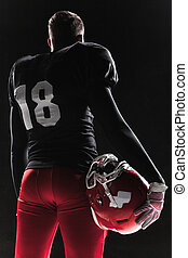American football player posing with ball on black...