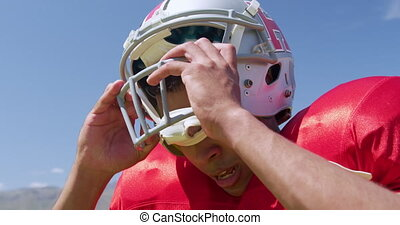 American football player removing helmet - Side view close ...
