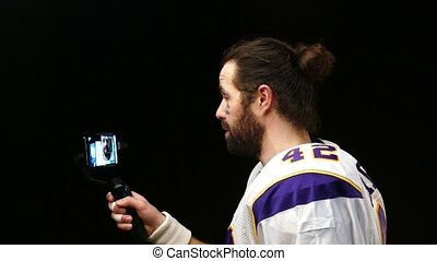 American Football Player reports to social networks using a smartphone