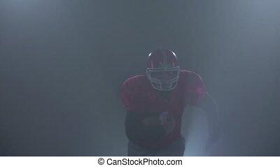 American football player runs on the camera. Smoky background studio