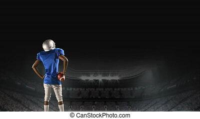 American football player standing on a field raising a ball