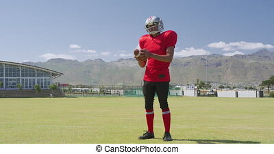 American football player standing with helmet and ball