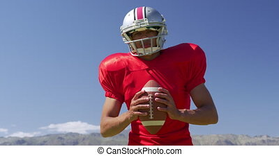American football player standing with helmet and rugby ball