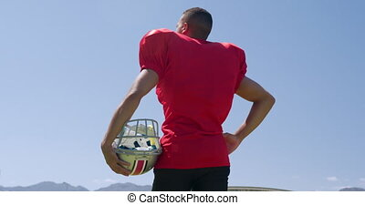 Rear view of a mixed-raced American football player holding his helmet, standing at a sports field against a blue sky, in slow motion. Track and Field Sports Training in Stadium.