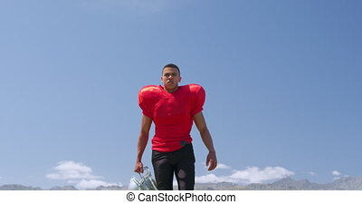 Low angle front view of a mixed-raced American football player holding his helmet and walking to camera at a sports field in slow motion. Track and Field Sports Training in Stadium.