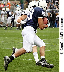American Football player with ball, turning to run
