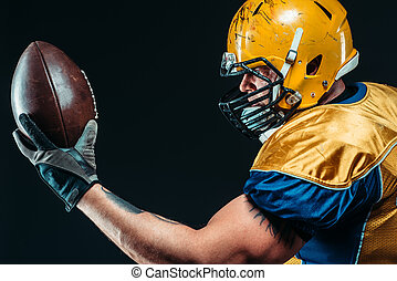 American football player with laced ball in hands