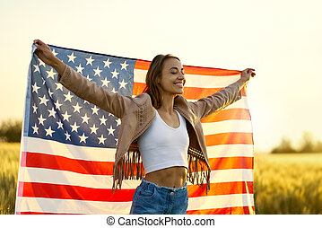 American freedom woman with open arms holding american flag at golden sunset field