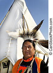 A Northern Cherokee man wearing a headdress and standing in front of a tee pee.