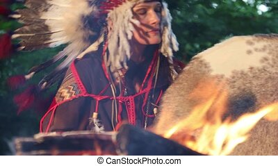 American Indian Shaman woman drumming in a trance at night in the forest by the fire