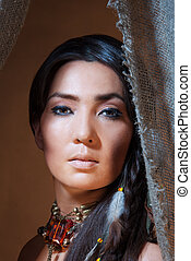 American Indian woman looking from the tent - studio photo...