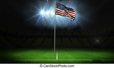 American national flag waving on flagpole against football...
