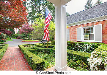 American old brick home with flag and classic garden.
