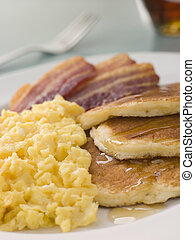American Pancakes with Crispy Bacon and Scrambled Eggs and Maple Syrup