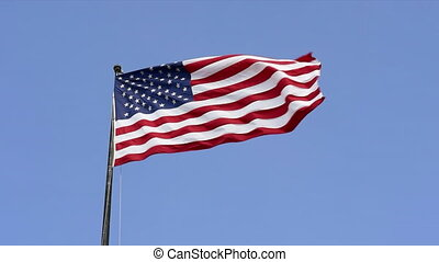 American patriot flag in the blue sky by sunny day.