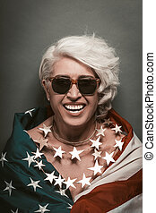 American patriotic woman celebrate Independence Day of USA. Senior woman laughs looking at camera wrapped in american flag wearing beads of stars