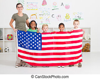 American preschool students and teacher holding a USA flag