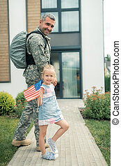 American serviceman returning home going to house with daughter