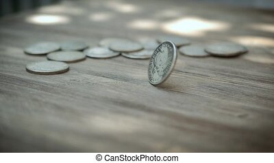 American silver coin rotating in slow motion onto a wooden table, and eventually settle.