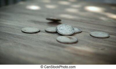 American silver coins falling in slow motion onto a wooden, rotating as they land and eventually settle