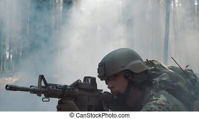 American soldier lies in ambush in smoke.