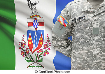 American soldier with Canadian province flag on background - Yukon