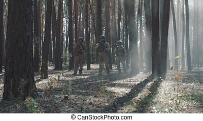 American soldiers patrol the perimeter in the forest.