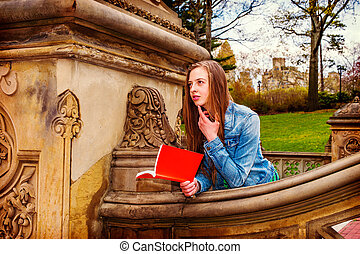 American Teenage Girl Reading Book Outside on Campus in New York