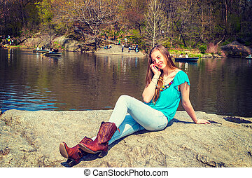 American Teenage Girl Talking on Cell Phone by lake at Central Park, New York
